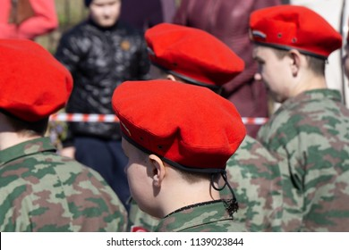 Military kid wearing red beret next to a Russian flag back view. Patriotic Young boy in a uniform at a parade . Russia Berezniki may 1, 2018