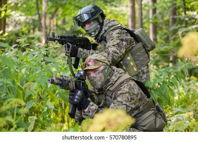 Military man in camouflage with guns in the woods