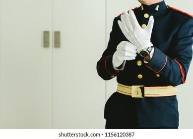 Military man hands putting on some elegant white gloves.