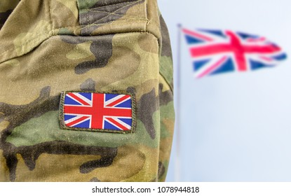 Military man posing in front of UK flag