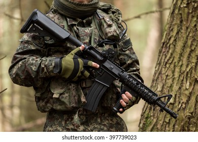 Military man with Rifle M16 outdoor forest, without a face
