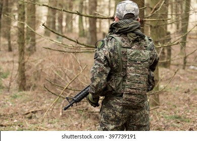 Military man with Rifle M16 outdoor forest, view from the back