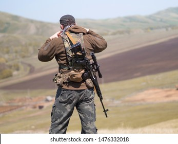 Military man with sniper rifle SVD, outdoor, view from the back. Middle eastern military conflict.