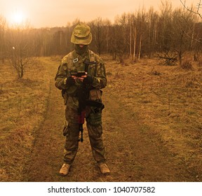Military man standing outdoors with a gun in his hands. sunset
