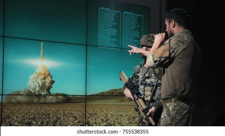 Military men in system control area watching nuclear missile launch looking at digital screen.