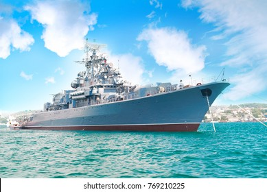 Military navy ship in the bay with blue sky and clouds