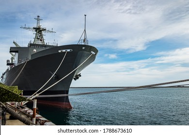 Military navy ship in the port. Gray modern warship with blue sky in the landscape sea. Battleship sonar boat defense with cloudy in the wharf.