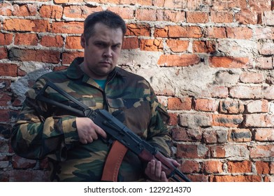 military on brick wall background.severe experienced military.military camp in the field.sharpening combat skills.shooting from a Kalashnikov assault rifle.AKS-74