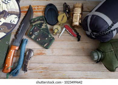 Military pack for soldier,army water canteen ,rope,light,campus,battery and mobile case,Military combat boots, combat knife ,hat on white wooden background,top view for copy space