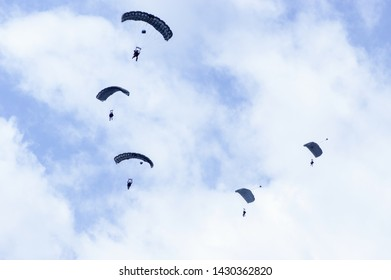 Military parachutists also called paratroopers in the sky with many clouds.