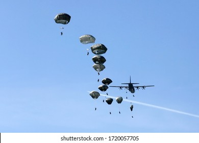 Military paratroopers jumping out of the transport plane.