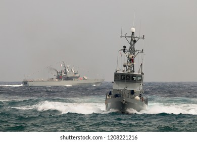 Military patrol boats entering port.