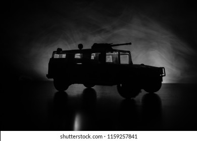 Military patrol car on dark toned foggy background. Army war concept. Silhouette of armored vehicle with gun in action. Decorated. Selective focus