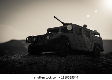 Military patrol car on sunset background. Army war concept. Silhouette of armored vehicle with gun in action. Decorated. Selective focus