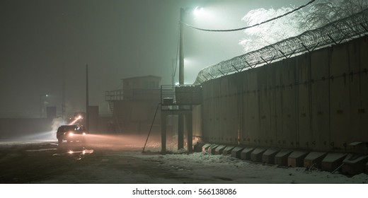 Military patrol at night along T Wall on Bagram Air Base during snow storm
