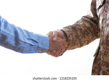 Military person and civilian shaking hands standing on white background