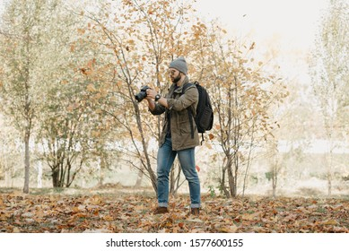 A military photojournalist with a beard in aviator sunglasses with mirror lenses, olive combat jacket, jeans and shirt with wristwatch holds the DSLR camera, checks photos near the battlefield