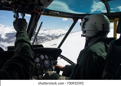 Military pilot and copilot flying a UH-3H Sea King helicopter over snowed mountains. Andes, Bariloche.