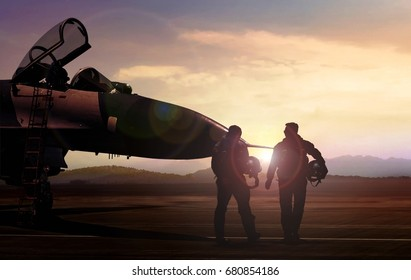 Military pilots on airfield during sunset