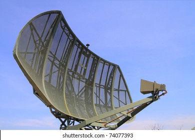 Military radar dish against blue sky