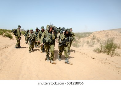 MILITARY RESTRICTED ZONE, ISRAEL - JUNE 4, 2013: Group of Israeli elite unit combat soldiers carrying a wounded friend on a stretcher through a sandy terrain after a fierce battle against terrorists.
