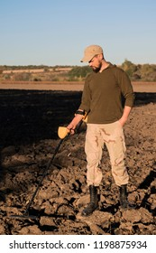 Military sapper with a metal detector examines the soil in the field for the presence of mines