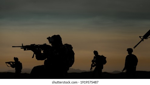Military silhouettes of soldiers against the backdrop of sunset sky