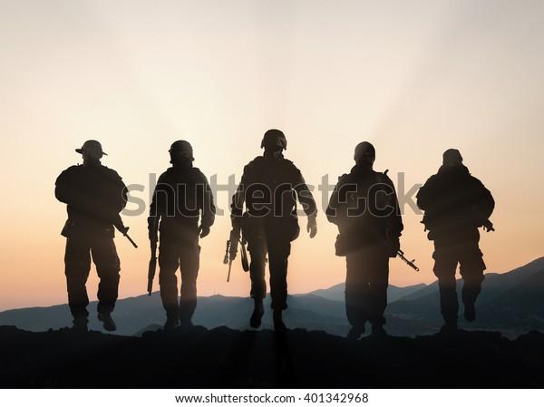 Militärische Silhouetten von Soldaten vor dem Hintergrund des Sonnenuntergangs am Himmel.