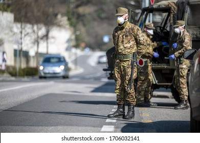 Military soldier controls on the street. Security patrol with masks and gloves monitor passing motorists. Daily street control for the Covid-19 global crisis. The army at work in the streets of Europe