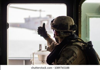 A military soldier in uniform making a thumbs up with his hand to a war helicopter at sea.