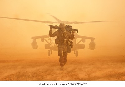 Military soldier walking at desert with gun on his shoulder in front of helicopter in sand storm.
