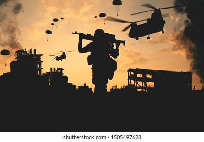 Military soldier walking in destroyed city with gun on his shoulder and parachute soldiers and helicopters in the sky