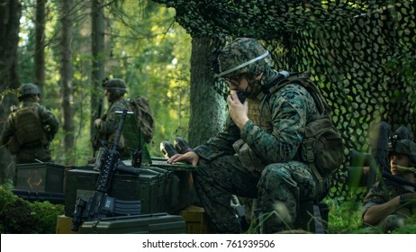Military Staging Base, Chief Army Engineer Uses Walkie-Talkie Radio and Army Grade Laptop. Squads Resides in Camouflaged Tent While Being on Reconnaissance Operation/ Mission.