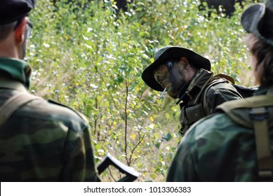Military style armored man in the forest. Air soft game.
