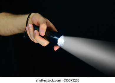 Military tactical flashlight in hand