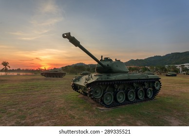 Military tank in the field during sunset.
