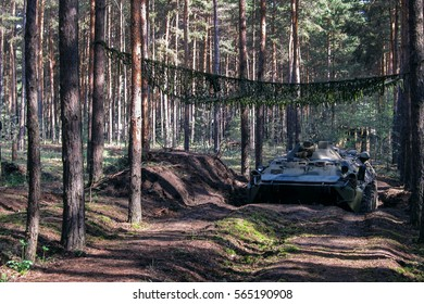 Military tank under the scrim on the forest road