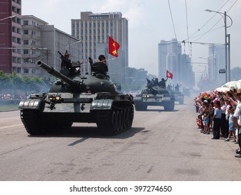 Military tanks parade in front of waving crowds through the streets of Pyongyang, North Korea, during 2013 Victory Day parade