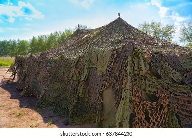 Military tent standing in the forest. Camouflaged tent countryside.