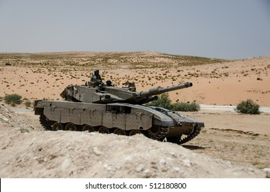 MILITARY TRAINING ZONE, ISRAEL - JUNE 4, 2013: Israeli Merkava tank in a desert landscape. Israel army Armored Corps military training to fight against terrorist anti-tank guerrilla squads.