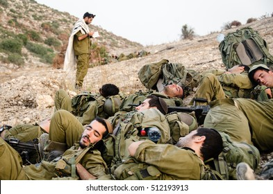 MILITARY TRAINING ZONE, ISRAEL - JUNE 4, 2013: Squad of Israeli soldiers are sleeping on the ground. Standing single soldier praying in the background. Exhausted soldiers after anti terror training.