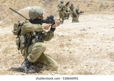 MILITARY TRAINING ZONE, ISRAEL - JUNE 17, 2015: Israel army soldier aiming an assault rifle while kneeling. Soldier firing at terrorist targets. Commando soldier shooting during combat training.