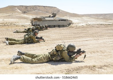 MILITARY TRAINING ZONE, ISRAEL - JUNE 17, 2015: Israel army combat soldiers firing an assault rifle. Infantry soldiers firing at targets. Warrior shooting in prone position during military training.