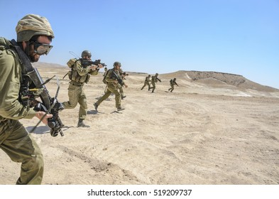 MILITARY TRAINING ZONE, ISRAEL - JUNE 17, 2015: Israel army combat soldiers firing an assault rifle while charging terror targets. Infantry warrior shooting while running during military training.