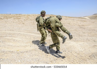 MILITARY TRAINING ZONE, ISRAEL - JUNE 17, 2015: Israeli army infantry soldier carrying his wounded fellow warrior, while another soldier is securing them. Wounded combat soldier is carried to safety.