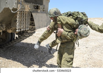 MILITARY TRAINING ZONE, ISRAEL - JUNE 17, 2015: Israeli army infantry soldier carrying his wounded fellow warrior during military training in the desert. Wounded combat soldier is carried to safety.