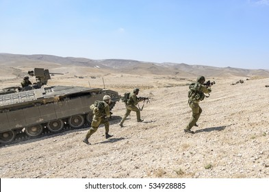 MILITARY TRAINING ZONE, ISRAEL - JUNE 17, 2015: Israeli army combat soldiers fire while storming the enemy. Infantry fighters shooting during military training in the desert, tank in the background.