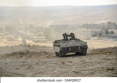 MILITARY TRAINING ZONE, ISRAEL - JUNE 17, 2015: Israel army Armored Personnel Carrier and town in the background. Israeli military armored vehicle during desert training, soldiers sticking out.