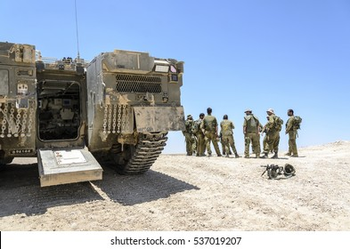 MILITARY TRAINING ZONE, ISRAEL - JUNE 17, 2015: Israeli army combat soldiers  debriefed after a military drill. Soldiers standing next to an armored personnel carrier. Soldiers next to a tank.