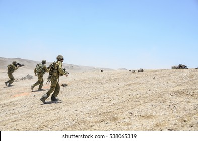 MILITARY TRAINING ZONE, ISRAEL - JUNE 17, 2015: Israeli army combat soldiers firing while charging terror targets. Infantry commando troops storming & shooting during military training in the desert.